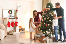 Family Decorating Beautiful Christmas Tree In Room