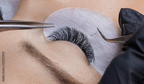 Canvas Print Eyelash extension procedure. Woman master making long lash