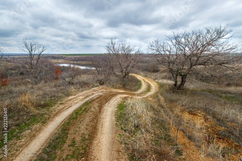 Fotografiet  The curved line of the rural road leading through the dry late fall grassland wi