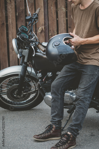 Carta da parati Handsome rider biker guy wearing black helmet and sitting on classic style cafe racer motorcycle
