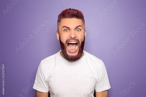 Fotografía Portrait of angry screaming man with dyed hair and beard on color background