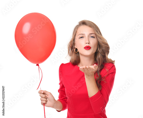 Photo  Beautiful young woman with balloon blowing kiss on white background