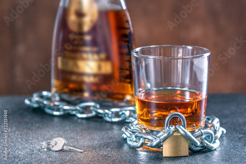 Fotobehang Alcohol Alcoholism concept, background with glass and bottle with whiskey locked on a chain.
