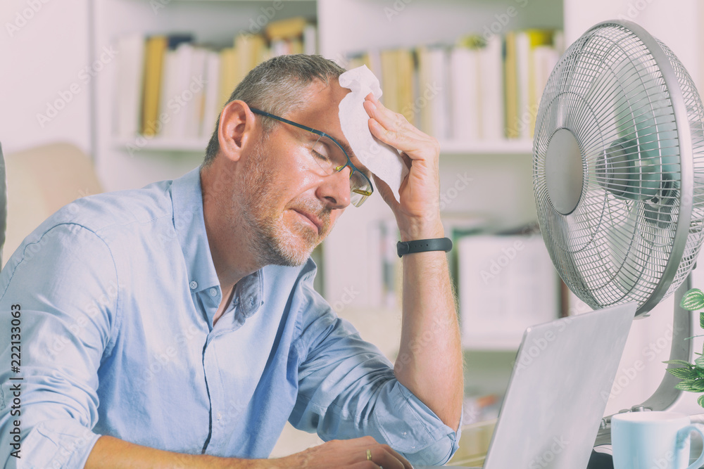 Fototapety, obrazy: Man suffers from heat in the office or at home