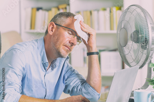 Fotografie, Obraz  Man suffers from heat in the office or at home
