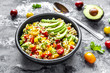 Bowl of bulgur salad with bell pepper, tomatoes, avocado, spring onion and parsley