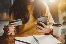 Young Beautiful Asian Woman Using Smart Phone And Credit Card For Shopping Online In Coffee Shop Cafe, Vintage Tone Color