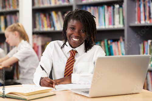 Canvastavla Portrait Of Female High School Student Wearing Uniform Working At Laptop In Libr
