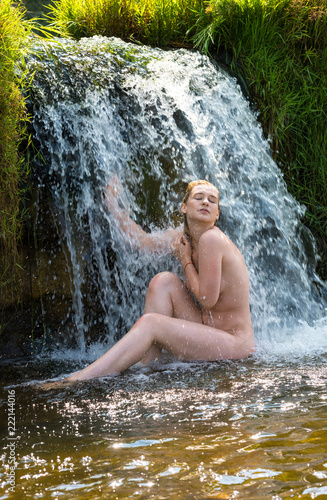 Tuinposter Akt Beautiful young nude woman enjoying summertime in waterfall.