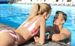 Happy young couple resting in swimming pool at resort