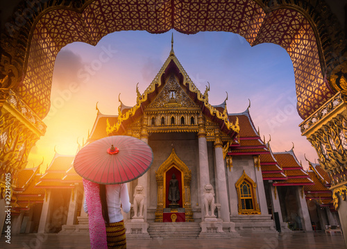 Woman holding traditional red umbrella on the Marble Temple, Wat Benchamabopitr Dusitvanaram at sunrise in Bangkok, Thailand Canvas Print