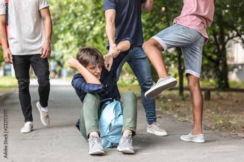 Aggressive teenagers bullying boy outdoors Fototapeta