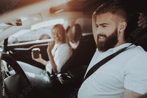 Fototapeta Man Is Driving A Tesla Car. Girl At Front Seat. obraz na płótnie