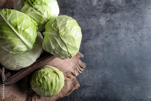 Photo Wooden box with fresh cabbages on grey table