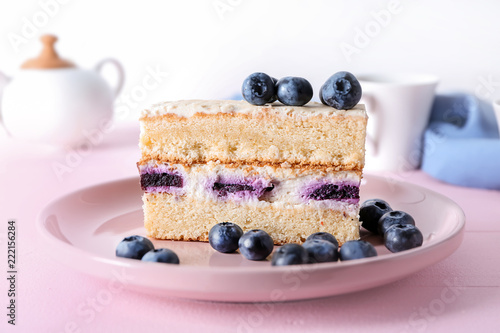 Tableau sur Toile Plate with piece of delicious blueberry cake on color wooden table