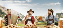 Germany, Bavaria. The Happy Smiling Singing Men With Beer Dressed In Traditional Austrian Or Bavarian Costume With Bavarian Pretzels Against Alpine Mountain Landscape. Oktoberfest, Festival Concept