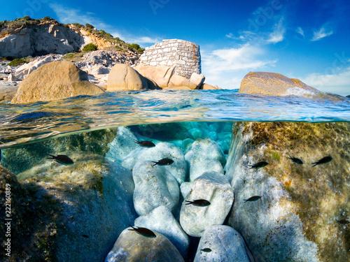 Half underwater whit black mediterranean fishes and granite rocks.