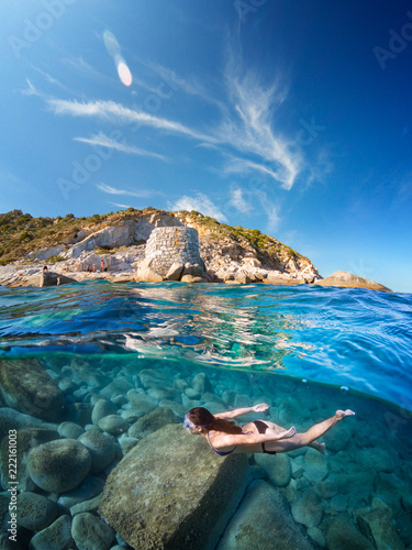 Half underwater with girl diving on a beautiful sea with granite cliff Fototapet