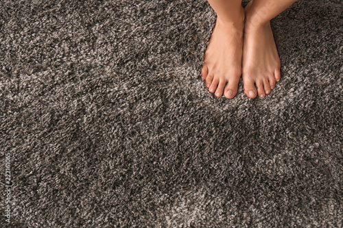 Foto Legs of barefoot woman standing on fluffy carpet