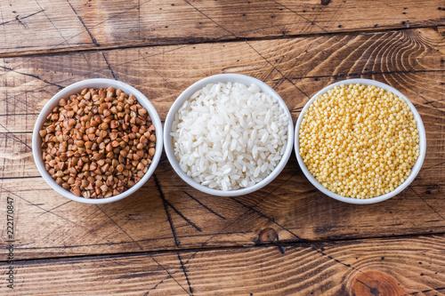Dry groats grocery. Rice, buckwheat and millet on the wooden background.