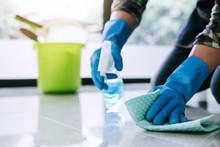 Housekeeper Man In Blue Rubber Gloves Using A Spray And A Duster While Cleaning On Floor At Home