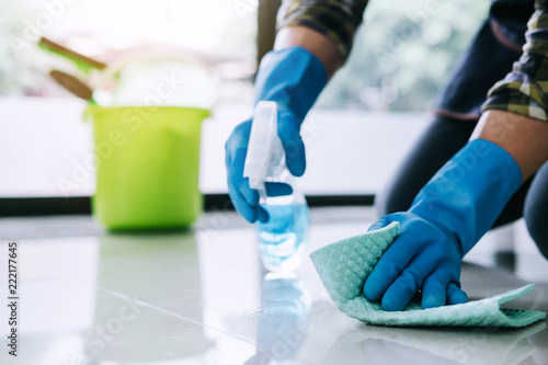 Housekeeper man in blue rubber gloves using a spray and a duster while cleaning Canvas