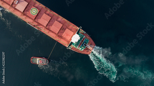 Fotografía  Aerial shot of a cargo ship approaching port with help of towing ship