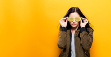 Fashionable Woman With Attitude In Bomber Jacket On A Golden Yellow Background
