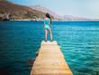 Young beautiful brunette girl on the pier of Preveli Beach (Palm Beach), Preveli, Crete (Greece)
