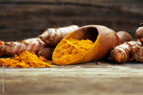Spoed Foto op Canvas Aromatische Turmeric powder and fresh turmeric on grey background