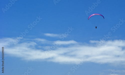 A paratrooper flies against a blue cloudy sky