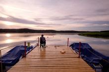 Local Fisherman Sitting On Pier And Fishing On The Lake At Early Morning In Summer.