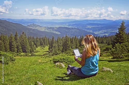 Stampa su Tela Close-up of woman reading e-book in nature