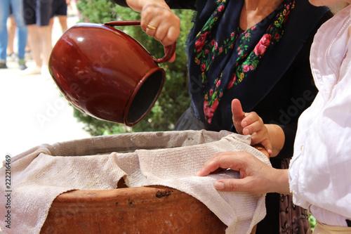 Fotografía  Mujer echando agua en un barreño para lavar a mano