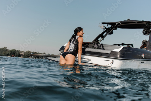 Attractive girl climbing on the motorboat on the lake