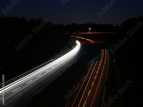 City landscape, automobile light trails, night highway traffic.