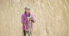 Female Photographer Standing In Tall Grass Capturing Pictures With Dslr Camera