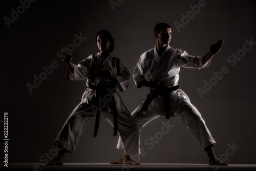 karate girl and boy posing against dark background