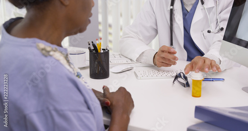 Valokuvatapetti Handsome young Hispanic doctor prescribing medication to senior woman for her lungs