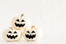 White Ghost Pumpkin On White Brick Block Background. Halloween Concept.