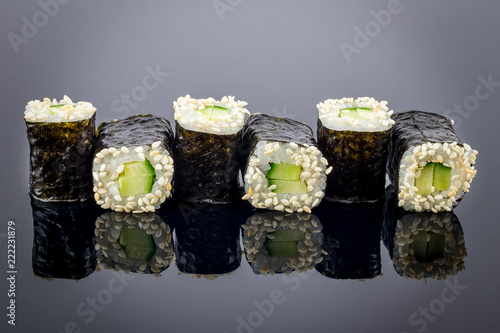 Fototapeta cucumber maki on black background with reflection obraz
