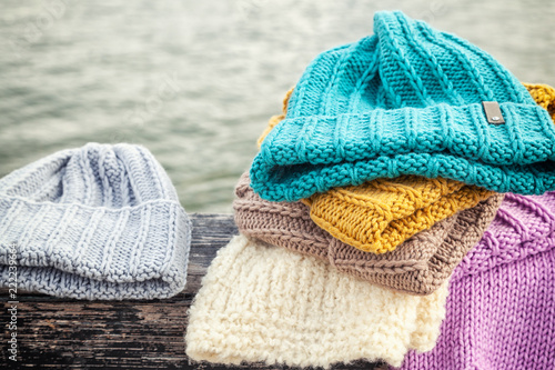 Obraz Beautiful background knitting winter blue and yellow a lot hat. Crochet hook handmade. Close-up of knitted hats of blue, yellow, pink and white - fototapety do salonu