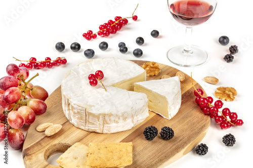 A photo of Camembert cheese with a glass of red wine, fruits and nuts, shot on a white background with copy space