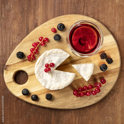 An overhead photo of Camembert cheese with a glass of red wine and fruits, on a dark rustic background with a place for text