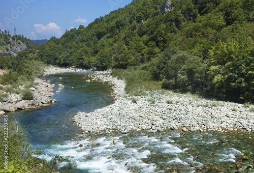 Foto op Aluminium Indonesië The pure turquoise water of the mountain river overcomes the stone rapids. Ecology concept, pure nature.