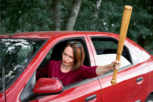 Fotografie, Obraz  young female driver has stress and anger, threatens with a baseball bat, has a r