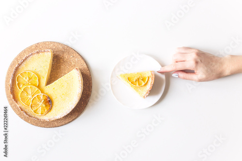 Lemon tart with dried lemons as a decoration and a cut piece in female hands Fototapeta