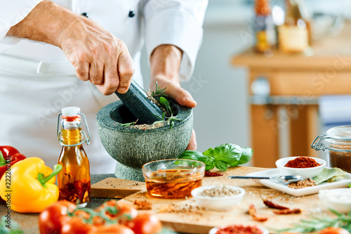 Man using pestle to grind food in small pot