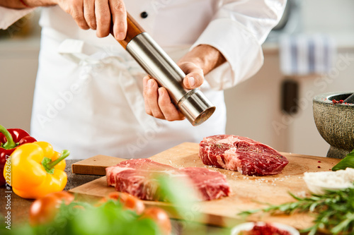 Side view of male chef grinding pepper for meat