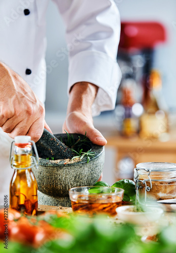 Chef using mortar and pestle to grind herbs